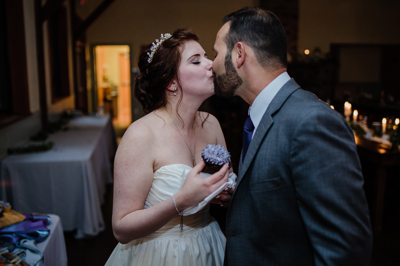 bride kissing groom while holding cup cake during candle light rustic themed wedding reception at Kwomais Hall by Kwomais Point Park in Ocean Park Surrey british columbia by best wedding photographer from Langley Mimsical Photography Christina Voorhorst style is documentary candid and fun photos