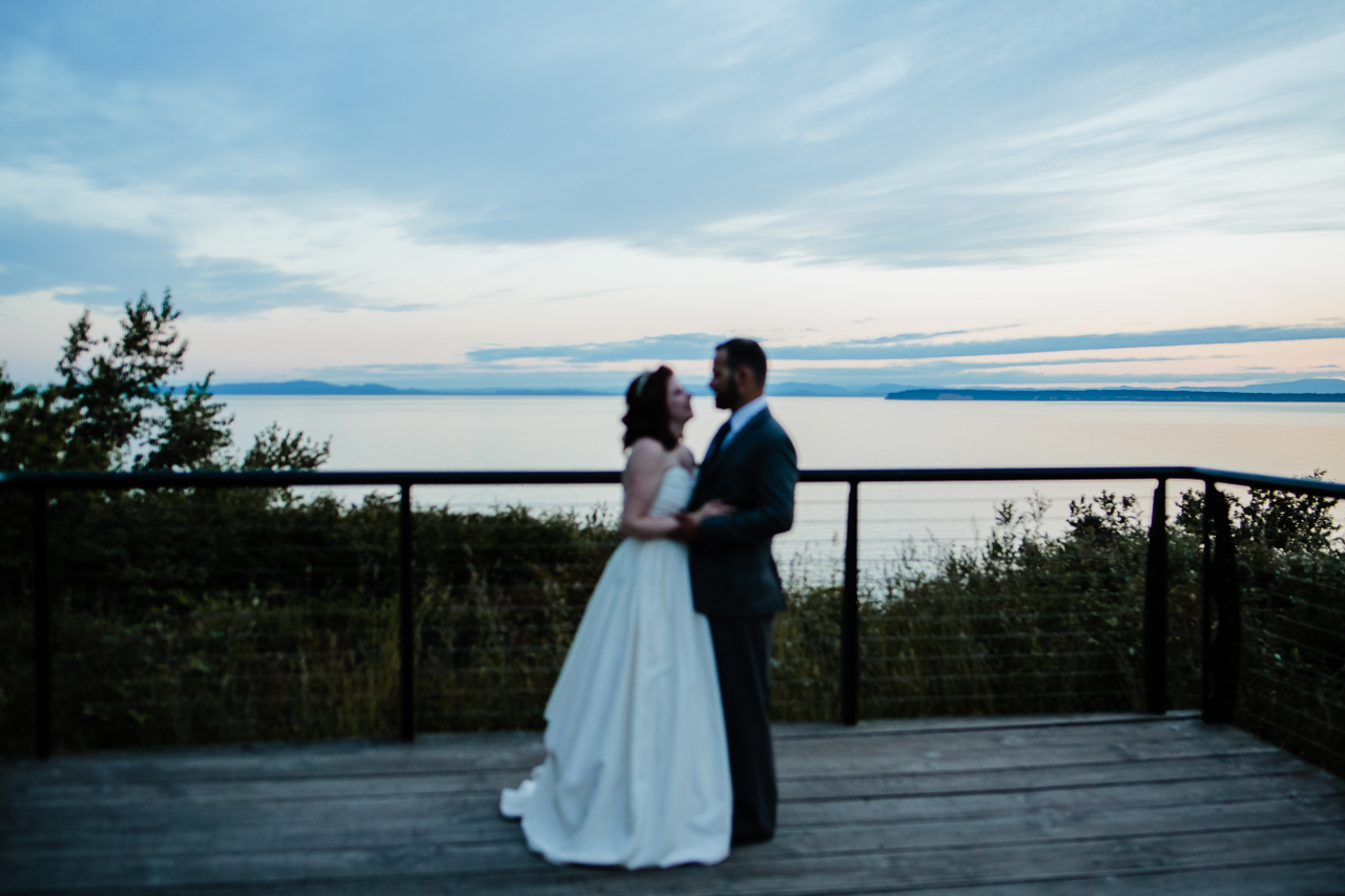 bride and groom standing at kwomais point lookout during sunset during candle light rustic themed wedding reception at Kwomais Hall by Kwomais Point Park in Ocean Park Surrey british columbia by best wedding photographer from Langley Mimsical Photography Christina Voorhorst style is documentary candid and fun photos