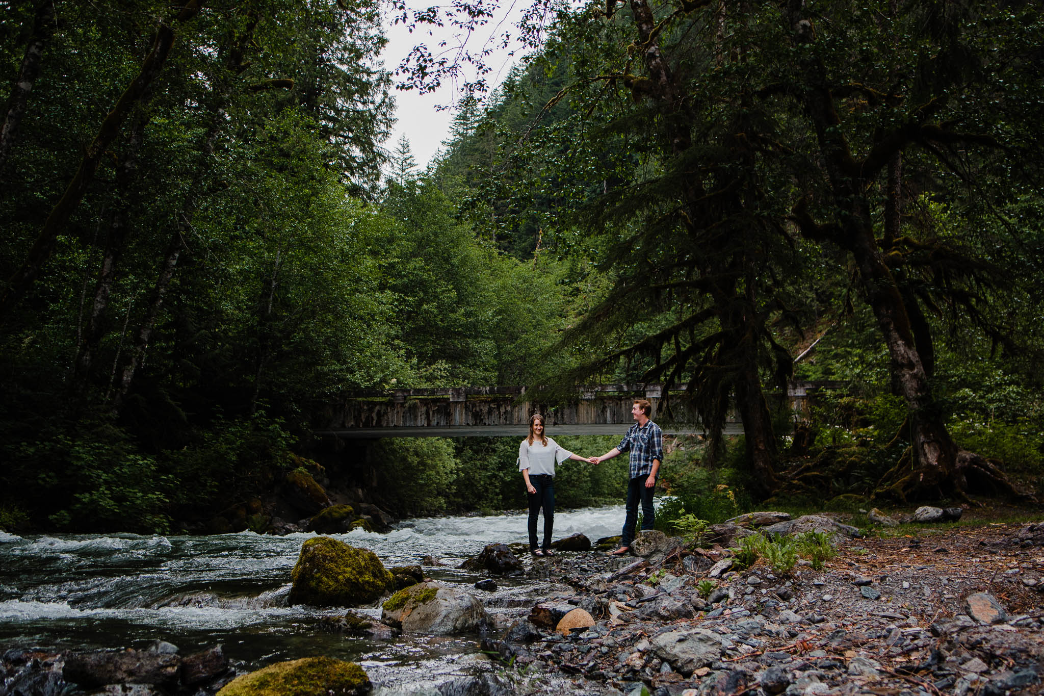 Couple holding hands standing by  Folley Creek near Folley lake in Chilliwack British Columbia during outdoor engagement photography session in the mountains with Mimsical Photography.    Outdoor adventure photographer based in Langley, British Columbia. Real fun engagement photos for outdoor enthusiasts in the lower mainland