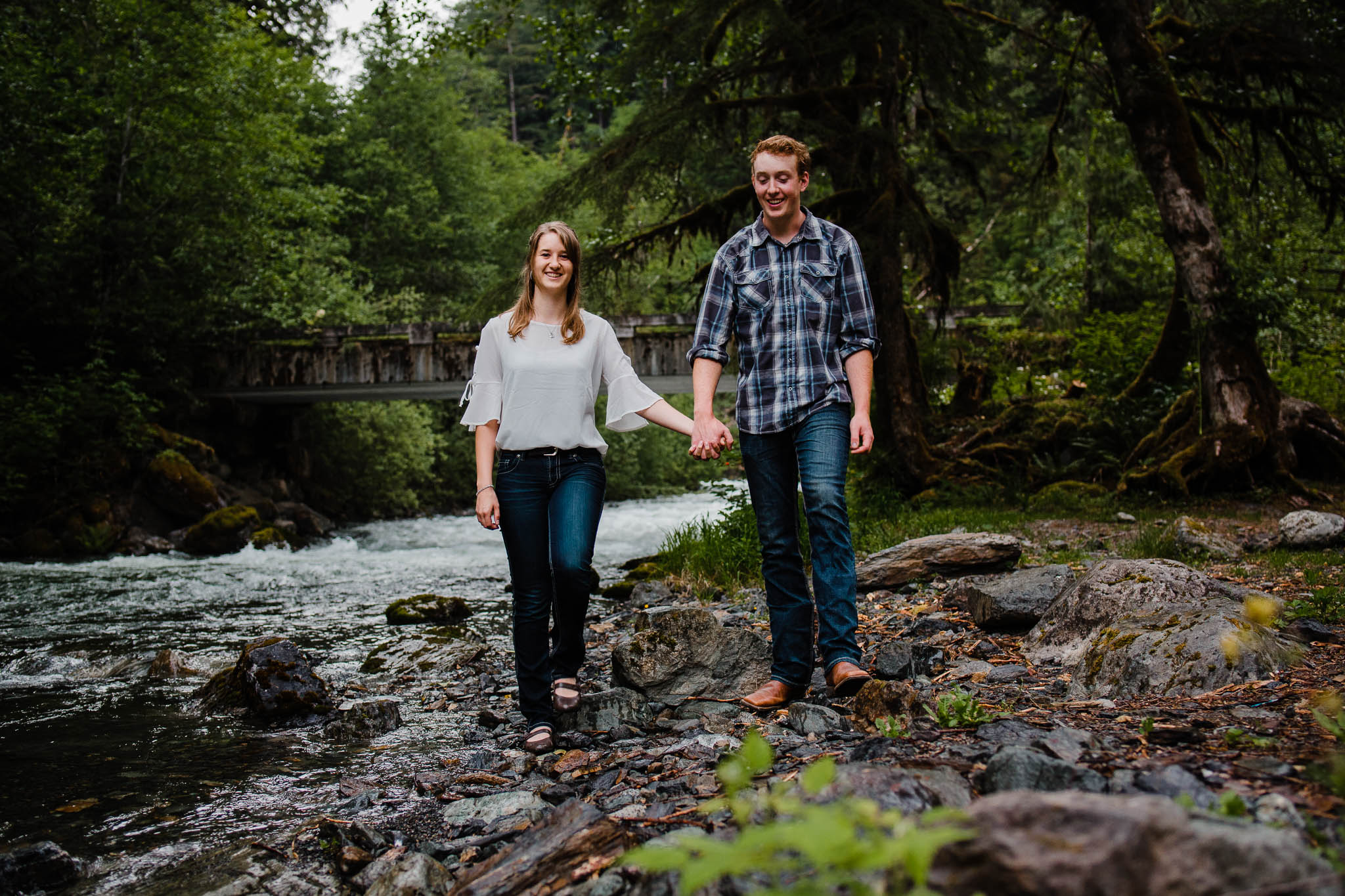Young couple holding hands wearing blue plaid and white shirt by  Folley Creek near Folley Lake in Chilliwack British Columbia during outdoor engagement photography session in the mountains with Mimsical Photography.    Outdoor adventure photographer based in Langley, British Columbia. Real fun engagement photos for outdoor enthusiasts in the lower mainland