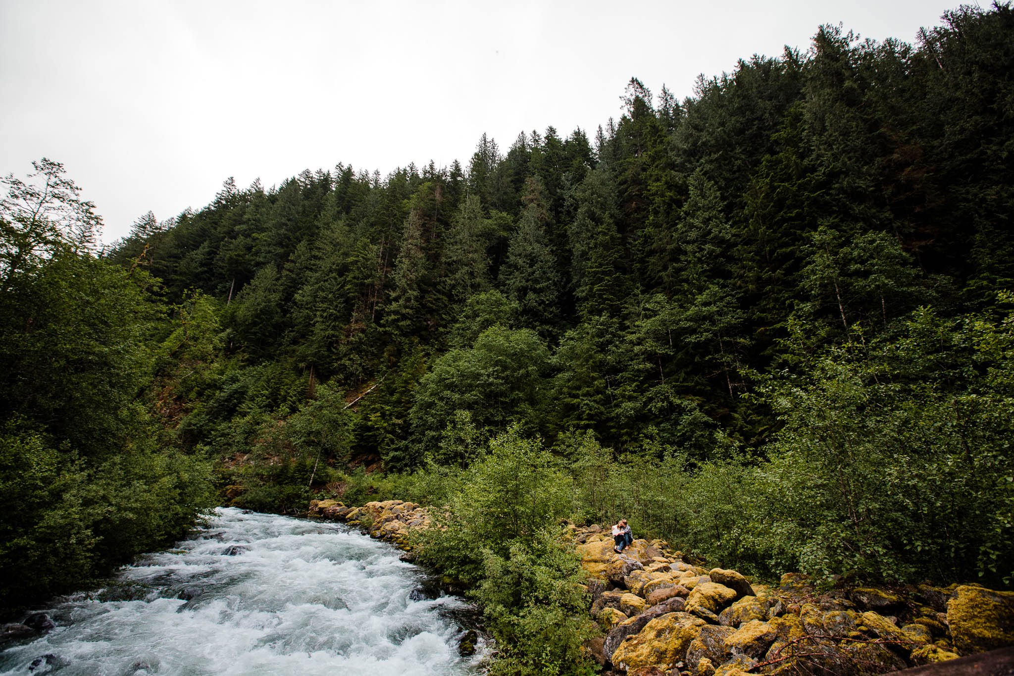 Wide angle picture of couple sitting on moss covered rocks in forest  by   Folley Creek near Folley Lake along Folley Service Road in Chilliwack British Columbia during outdoor engagement photography session in the mountains with Mimsical Photography.    Outdoor adventure photographer based in Langley, British Columbia. Real fun engagement photos for outdoor enthusiasts in the lower mainland. romantic pictures of couple