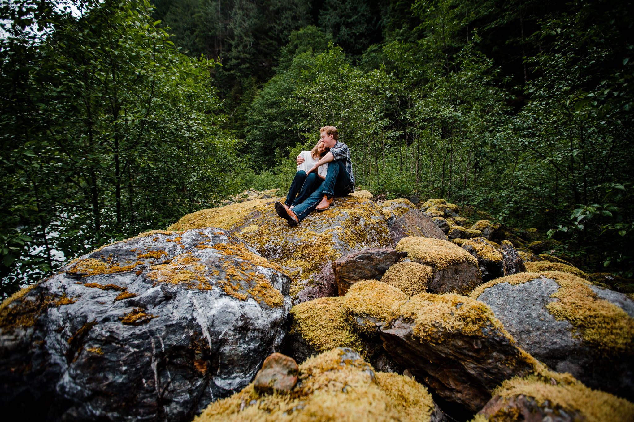 Wide angle photo of couple cuddling on moss covered rock  by   Folley Creek near Folley Lake along Folley Service Road in Chilliwack British Columbia during outdoor engagement photography session in the mountains with Mimsical Photography.    Outdoor adventure photographer based in Langley, British Columbia. Real fun engagement photos for outdoor enthusiasts in the lower mainland. romantic pictures of couple