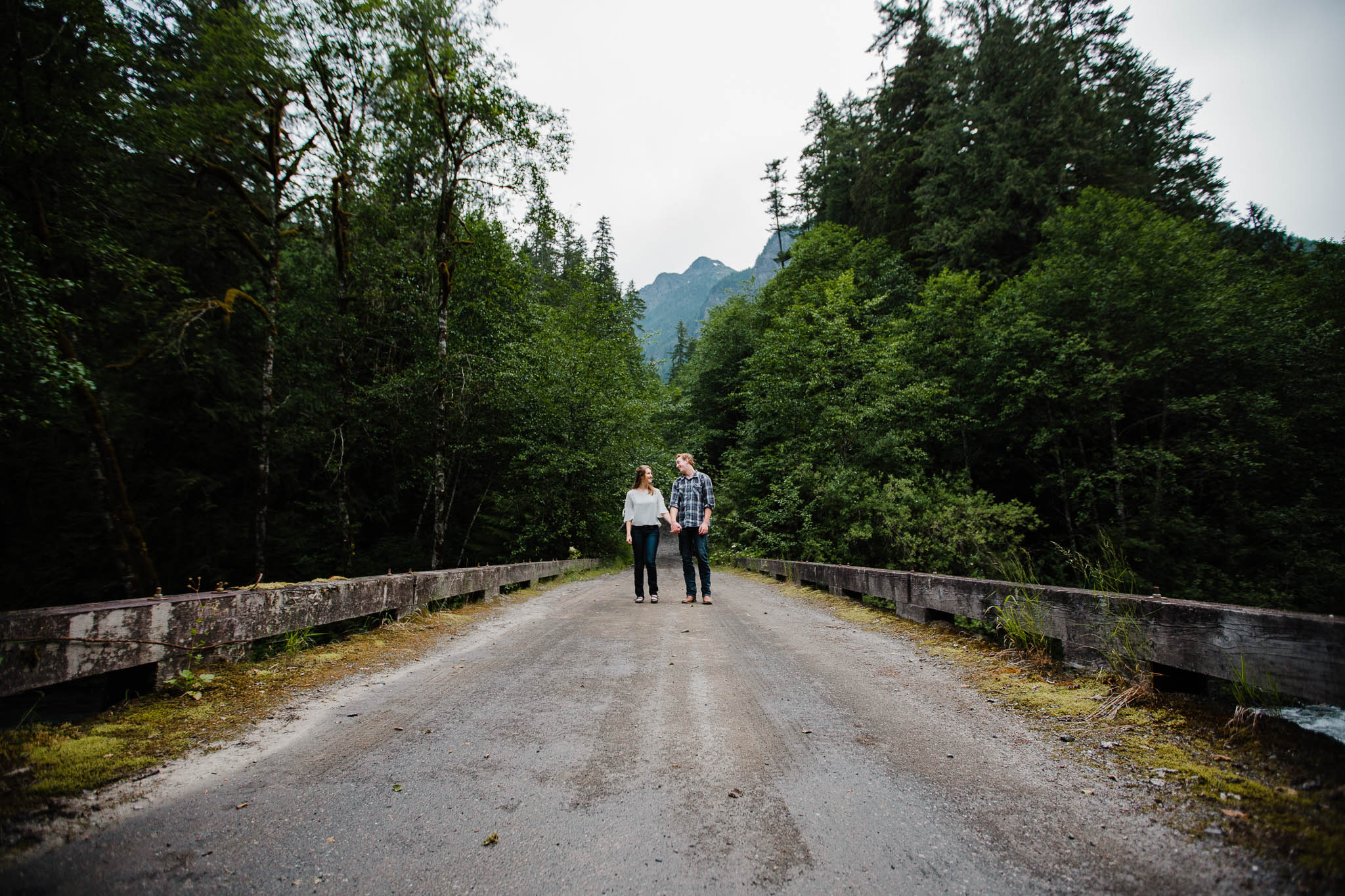 Couple standing on old service road bridge  by   Folley Creek near Folley Lake along Folley Service Road in Chilliwack British Columbia during outdoor engagement photography session in the mountains with Mimsical Photography.    Outdoor adventure photographer based in Langley, British Columbia. Real fun engagement photos for outdoor enthusiasts in the lower mainland. romantic pictures of couple