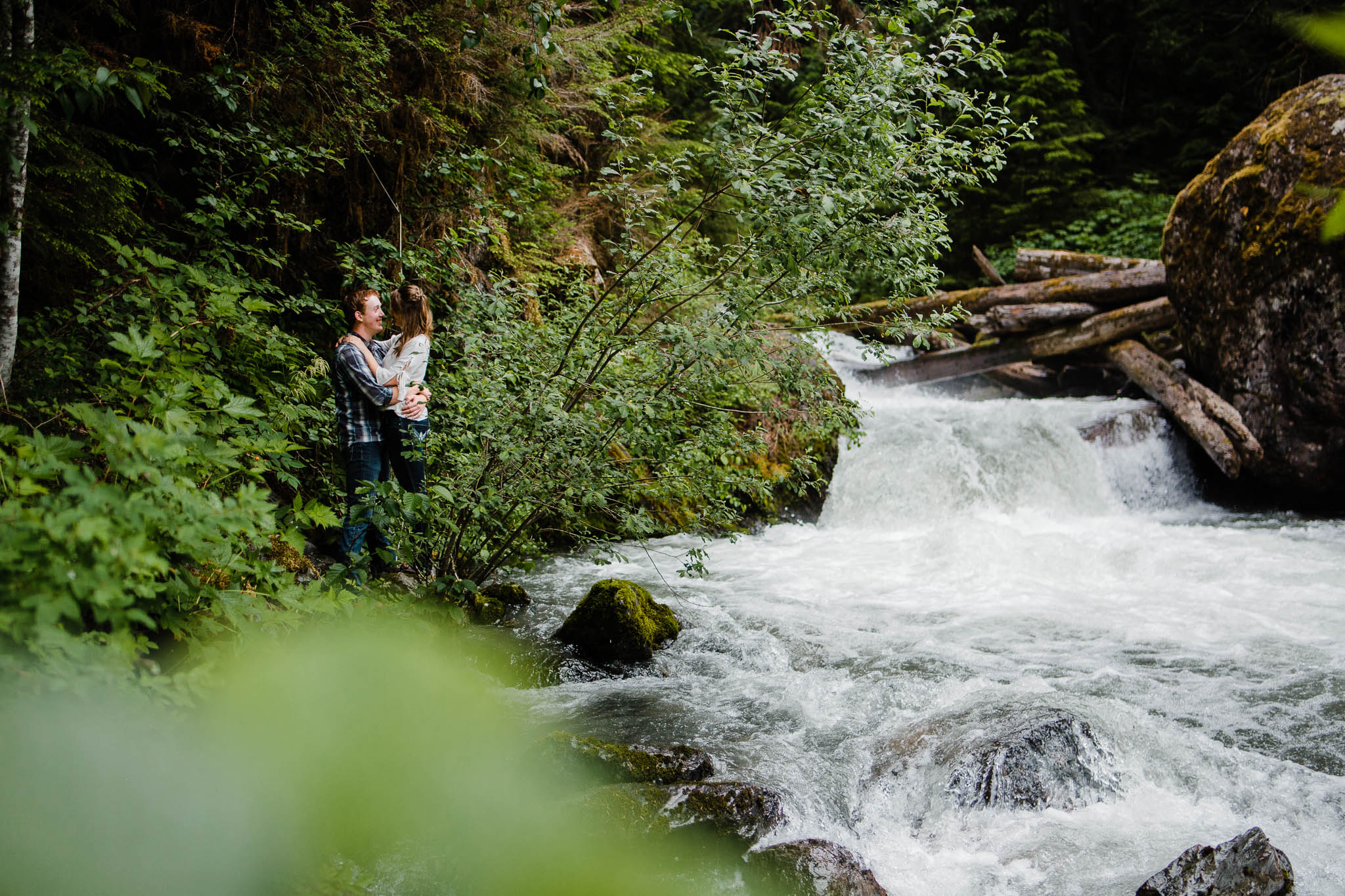 Wide angle photo of couple standing near Baby Munday Falls  by   Folley Creek near Folley Lake along Folley Service Road in Chilliwack British Columbia during outdoor engagement photography session in the mountains with Mimsical Photography.    Outdoor adventure photographer based in Langley, British Columbia. Real fun engagement photos for outdoor enthusiasts in the lower mainland. romantic pictures of couple