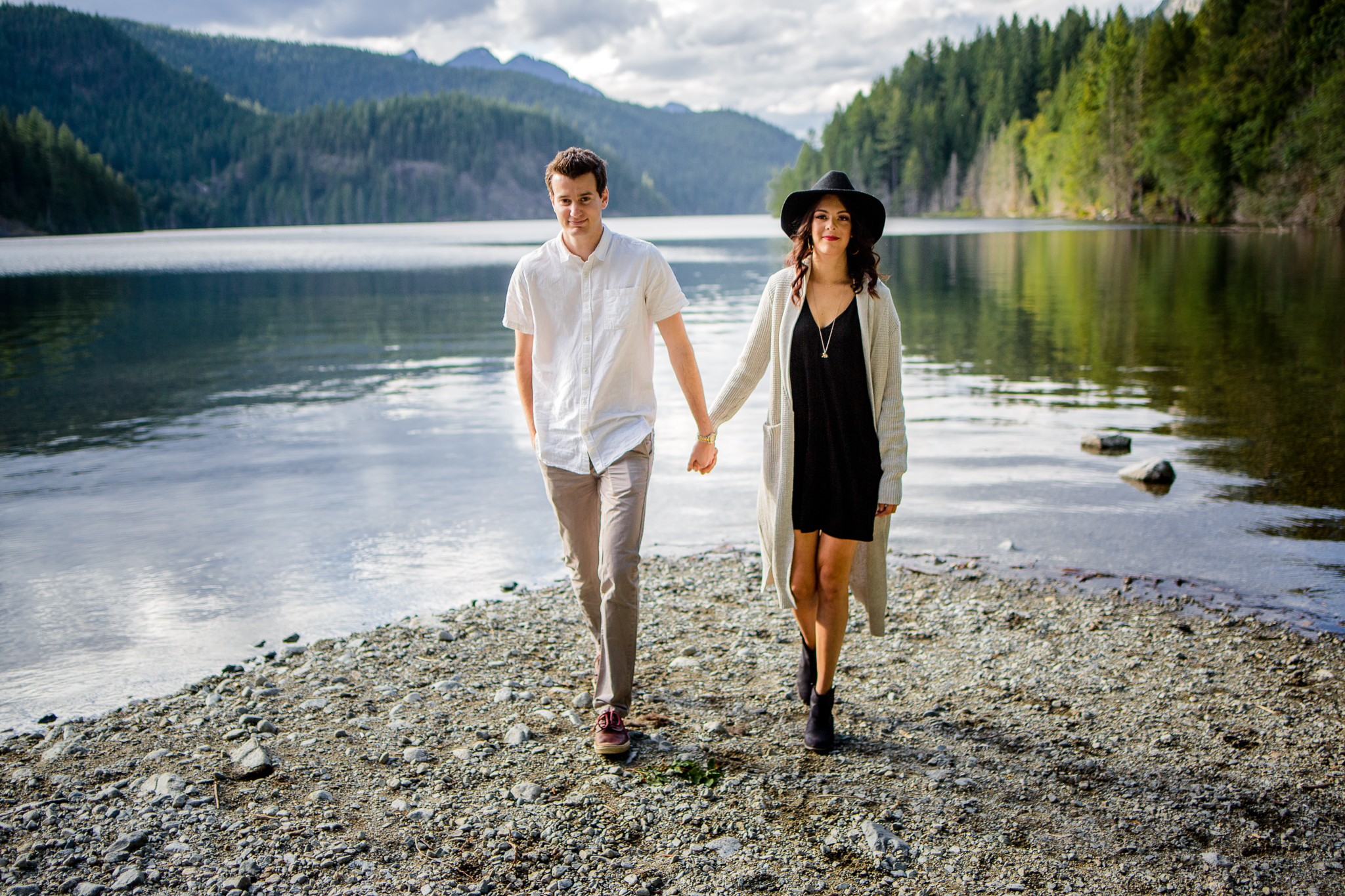 Couple walking towards camera holding hands with Buntzen Lake Landscape behind them evening still water wearing white button down shirt and black dress with hat during fun and romantic engagement photo shoot at Buntzen Lake, Port Moody, Anmore British Columbia by best couples photographer Mimsical Photography