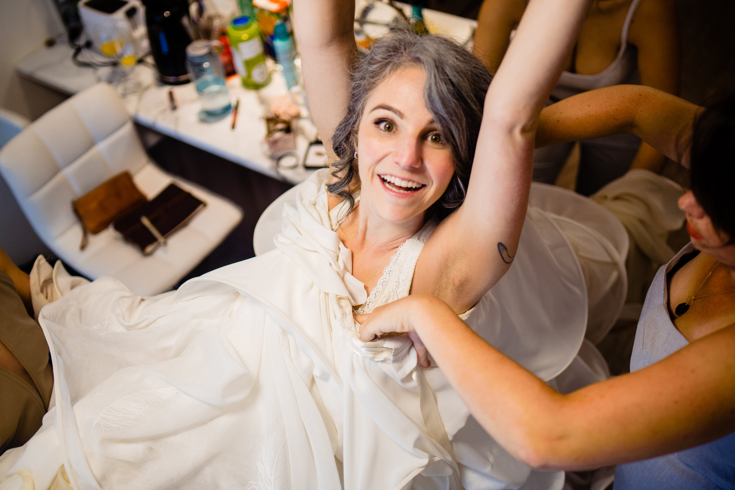 Bride getting in to her handmade dress during bridal prep  Cuckoo Trattoria and Pizzeria Wedding Photographer Vancouver Island Coombs, BC Goats on the Roof Market. Eclectic Formal quirky DIY artistic wedding full of handmade details and laughter. #fun #candid #storytelling #storytellingphotographer #bride #groom #weddinginspo #realwedding #horns #handmade #DIYwedding #DIYinspo #handmaderings #nobouquet #outdoor #pizzeria