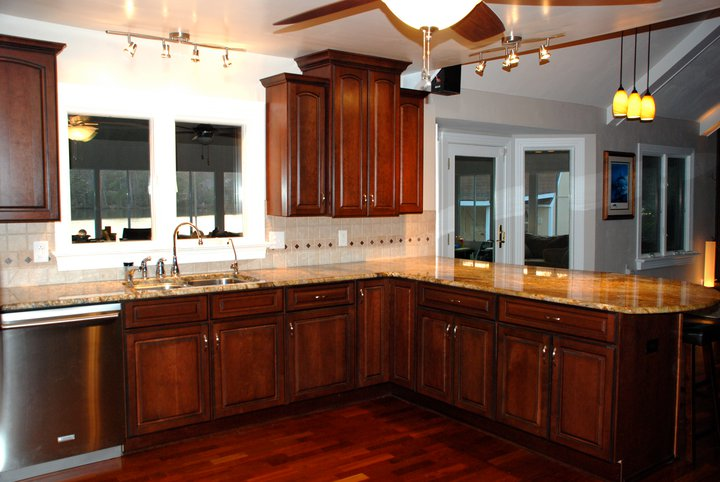 Staggered Height All Wood Cherry Raised Panel Cabinets.