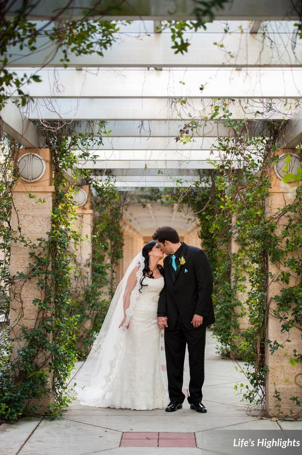 The bride wore a slim fit lace gown with embroidered detail under the bust line, and a long mantilla-style veil.