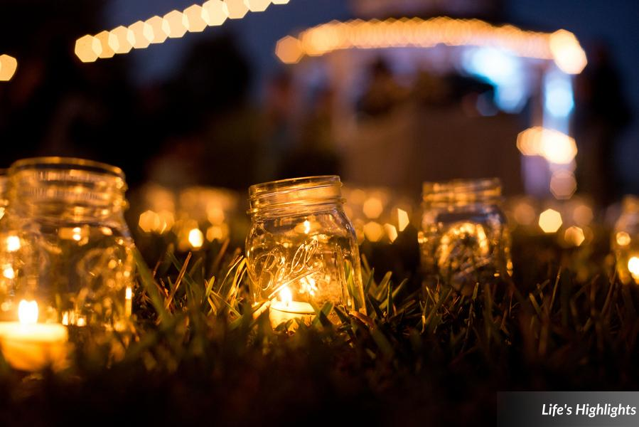 Mason jars filled with candles created a pattern of flickering light throughout the nearby lawn