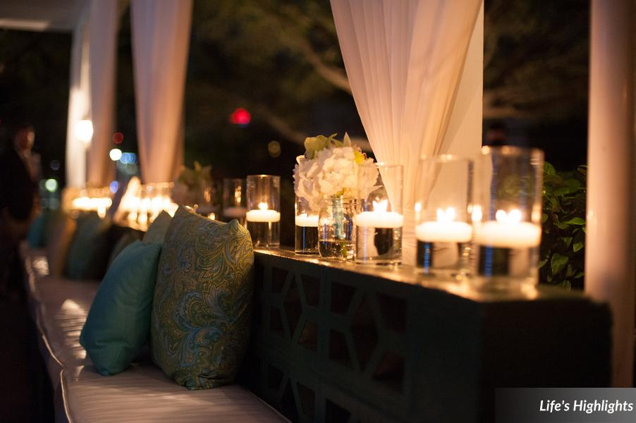 The veranda bench was accented with colorful pillows, and lined with floating candles and bridesmaid bouquets