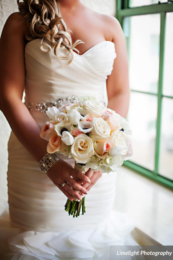 The bride carried a bouquet of hydrangea, roses, tulips, and amenomes