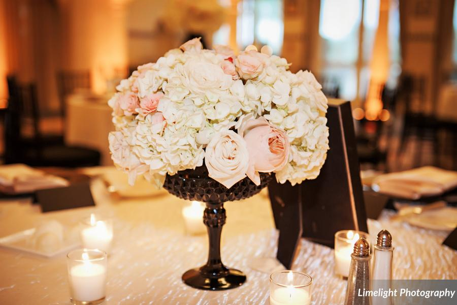 Centerpieces of glossy black vases filled with ivory and blush hydrangea, roses, and anemones