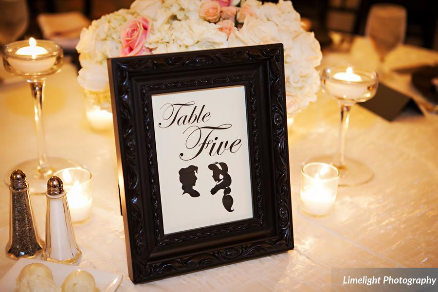 Table numbers of framed Disney couples silhouettes that corresponded with seating chart song lyrics