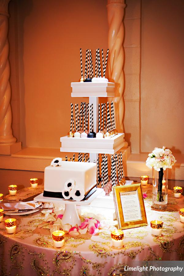 A display of assorted cake pops stood beside a chic wedding cake for the bride and groom to cut