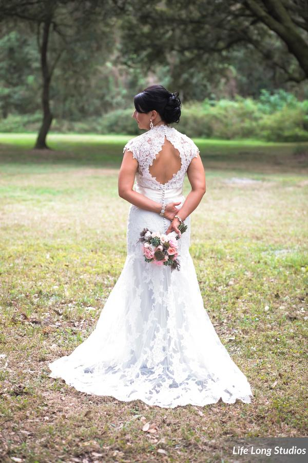 The bride wore a lace gown with keyhole back and carried a bouquet accented with bird nests and feathers.