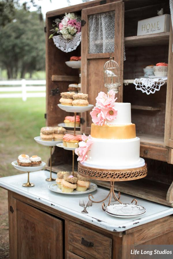 The gold-painted cake and nest-topped cupcakes were displayed on floral china atop a rustic hutch.