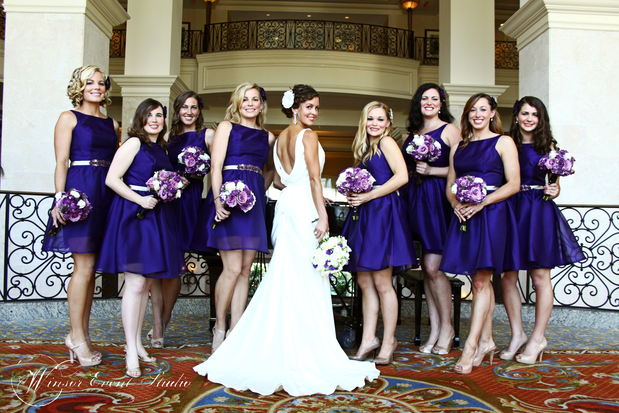 Bridesmaids wore deep purple Lazaro dresses and the bride wore a stunning cowl back gown.