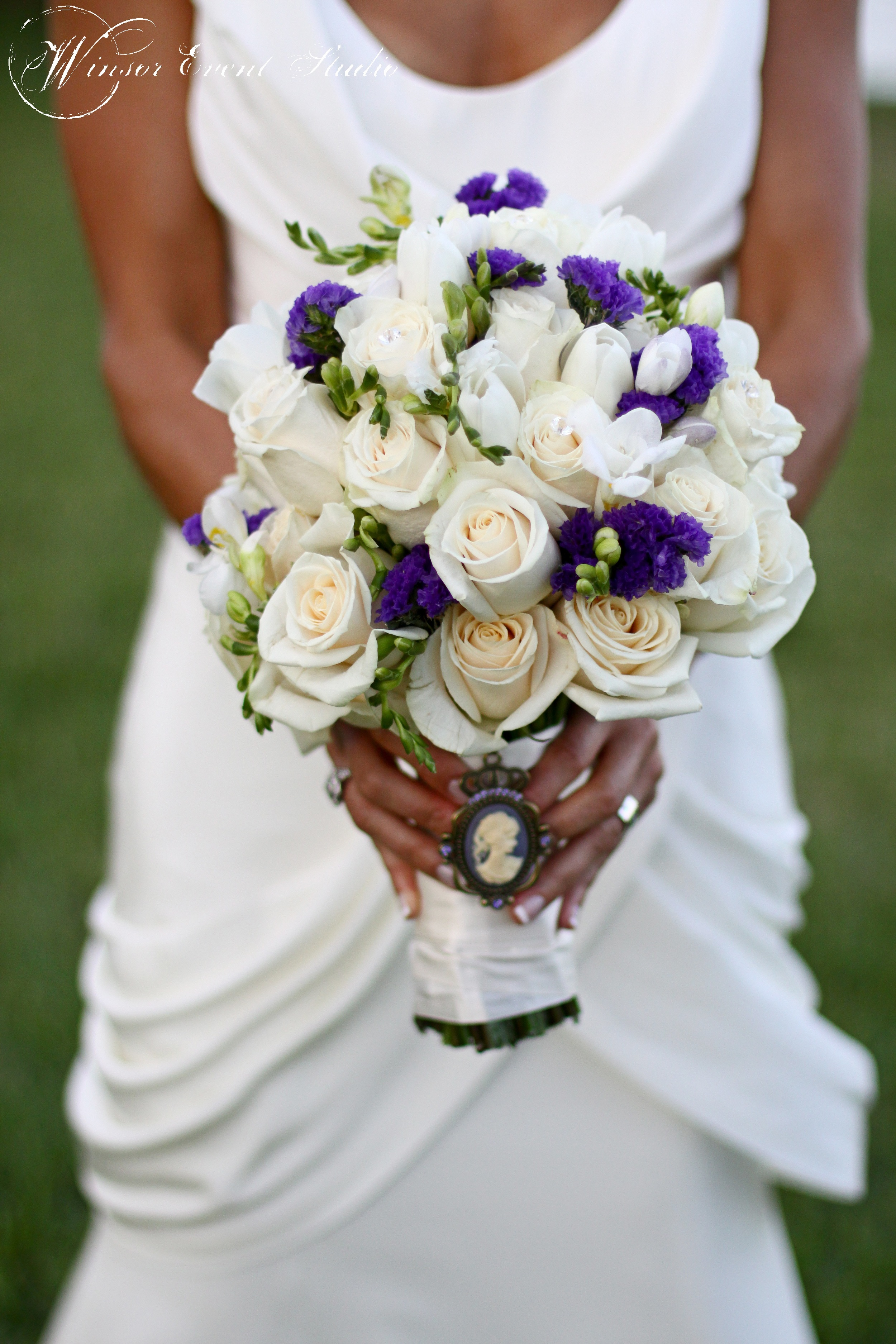 The bride's bouquet featured white roses, tulips, and freesia, with pops of purple and a vintage brooch.
