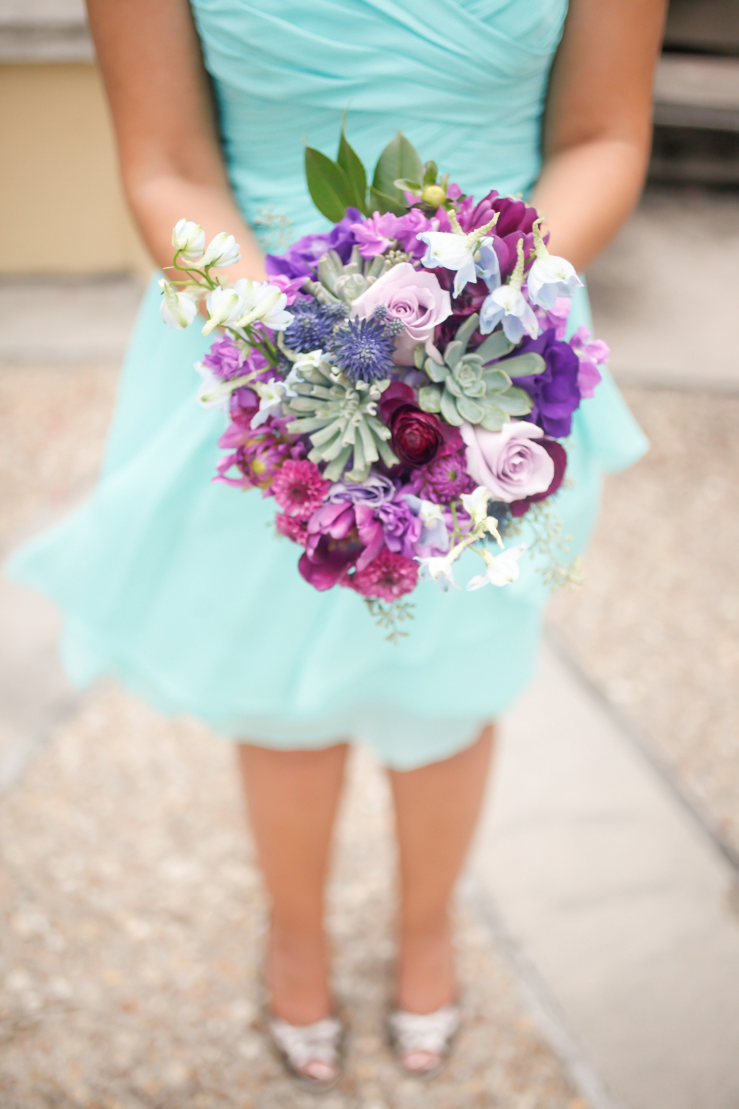 Bridesmaids carried bouquets in various shades of purple, accented with blue-hued succulents