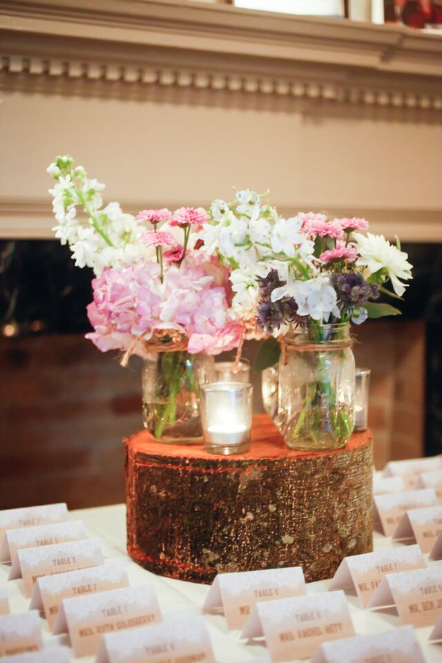 Cut log risers and mason jars filled with flowers accented the lace motif escort cards display