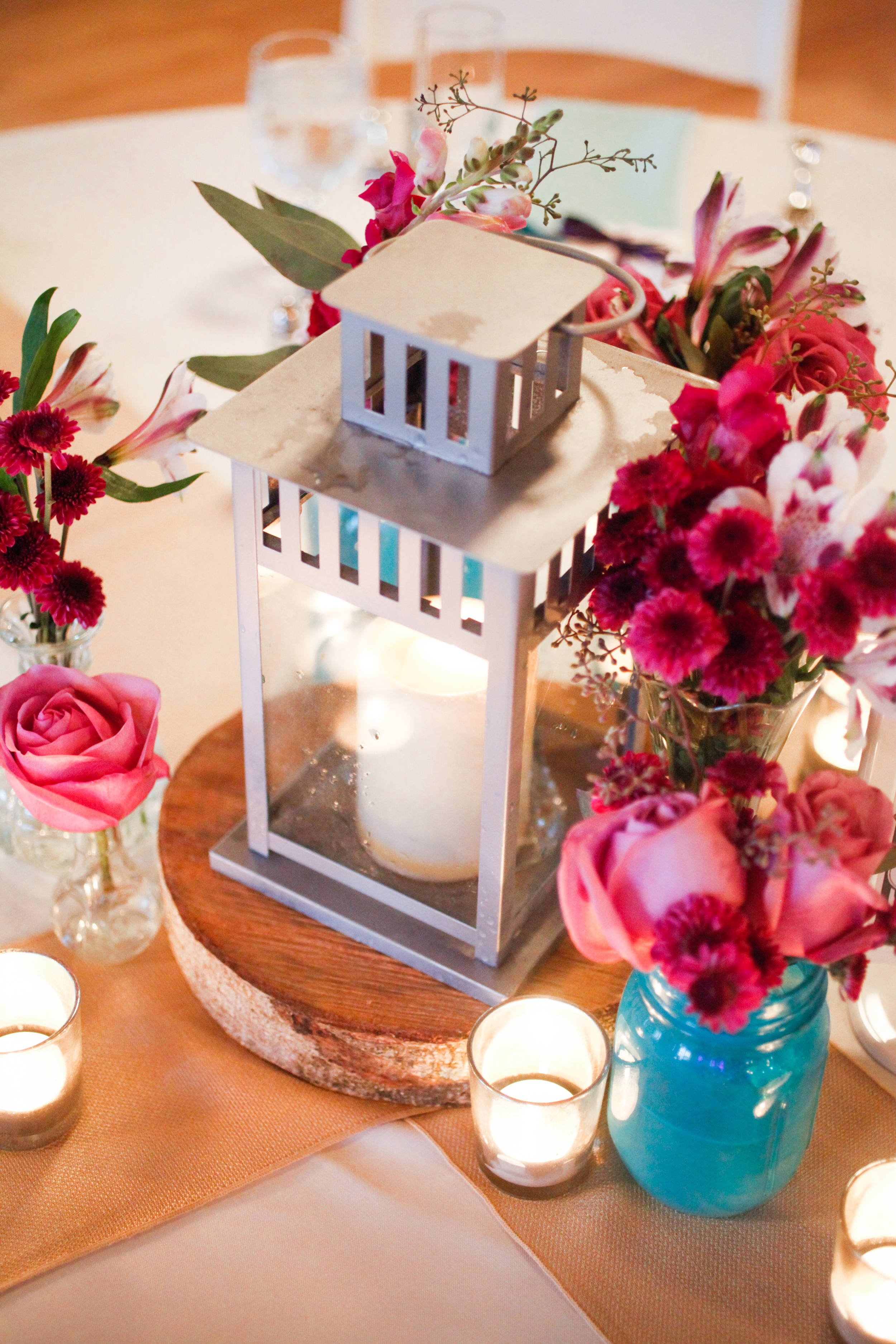 Centerpieces of silver lanterns were accented by mason jars, bud vases, & mercury glass votives.