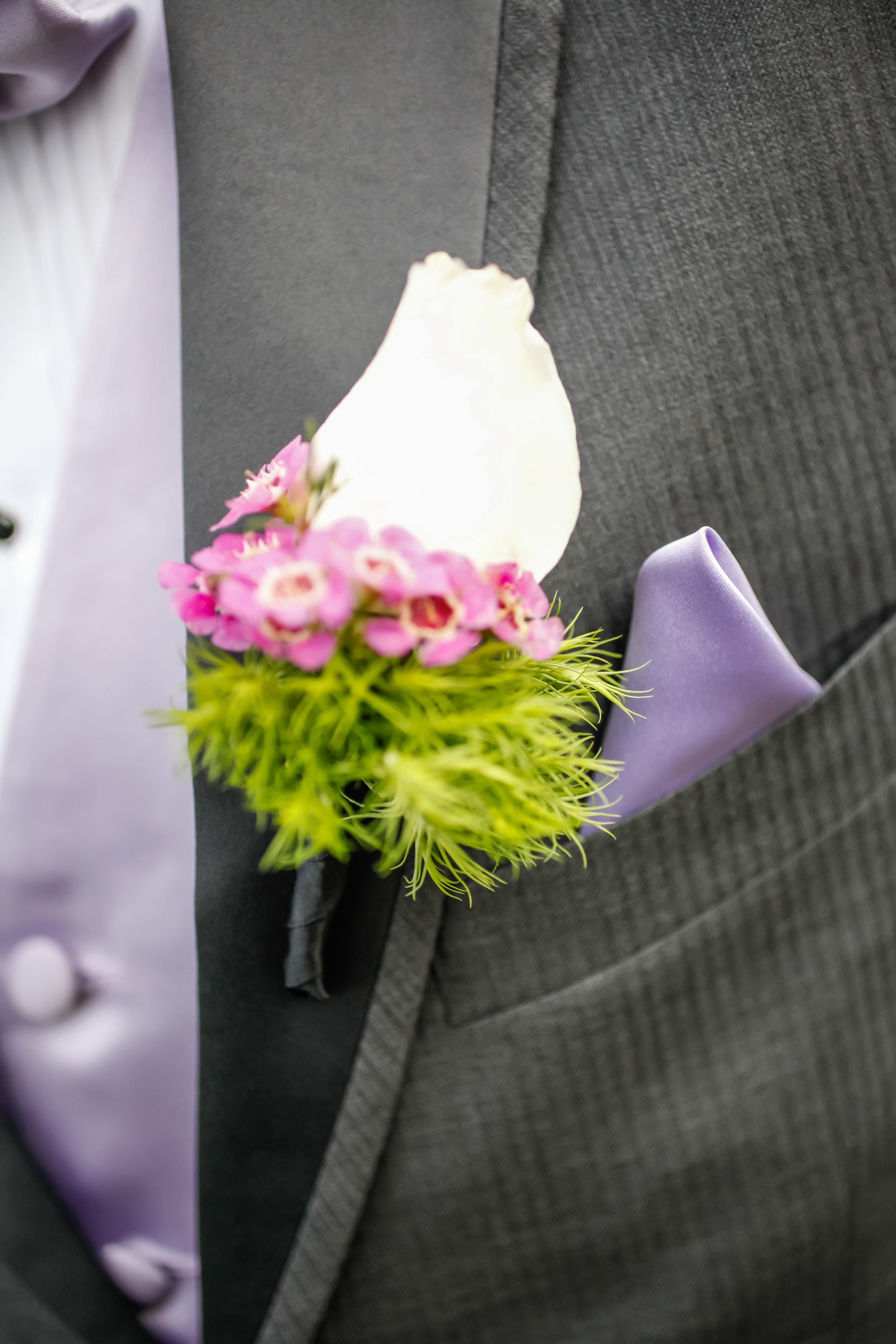 Boutonnieres included roses, waxflowers, and soft greenery.