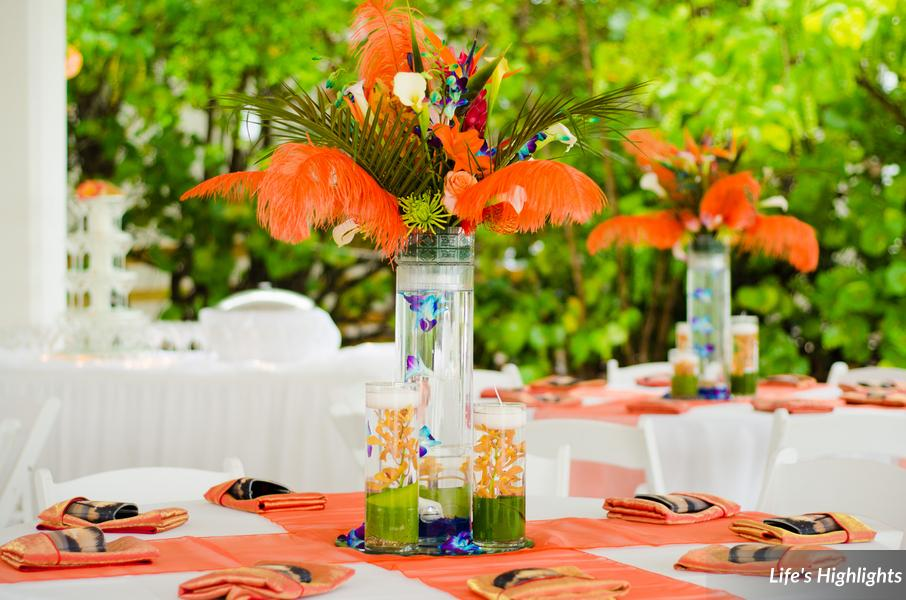 Tall centerpieces of tropical flowers, palms, &feathers were surrounded by submerged orchids &floating candles