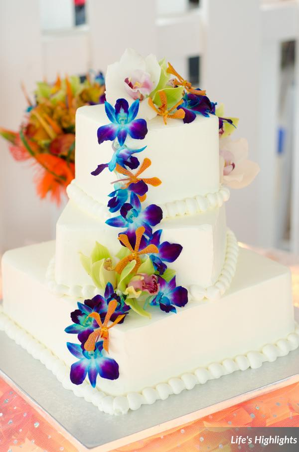Tropical orchids cascaded down the buttercream tiers of the wedding cake