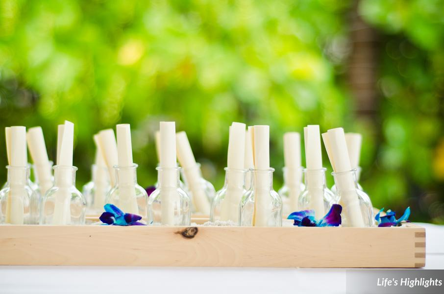 In honor of the couple's proposal story, programs were rolled and tucked into mini bottles nestled in sand