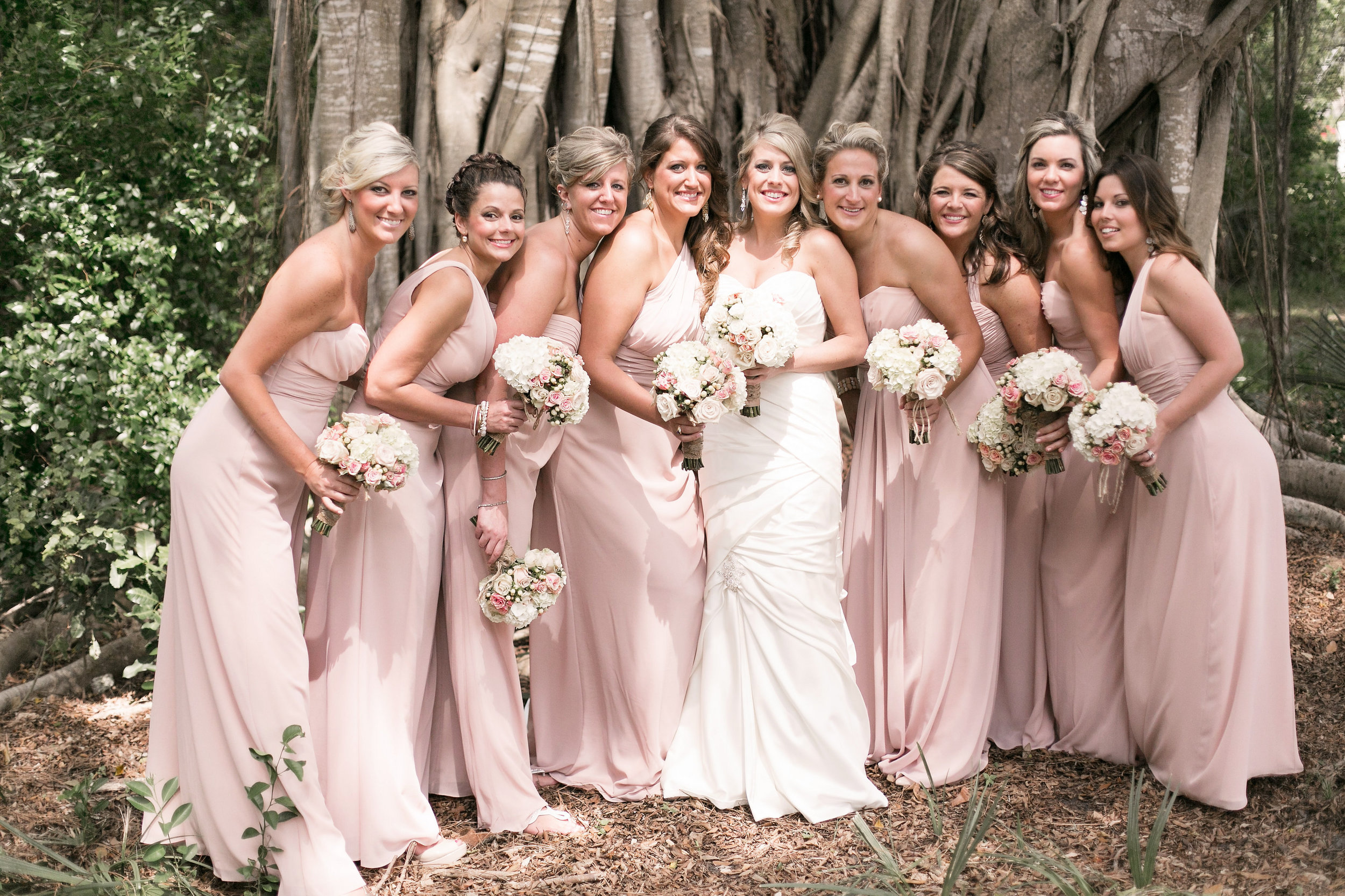 Bridesmaids wore blush hued crinkle chiffon gowns and carried bouquets of white hydrangea and blush roses