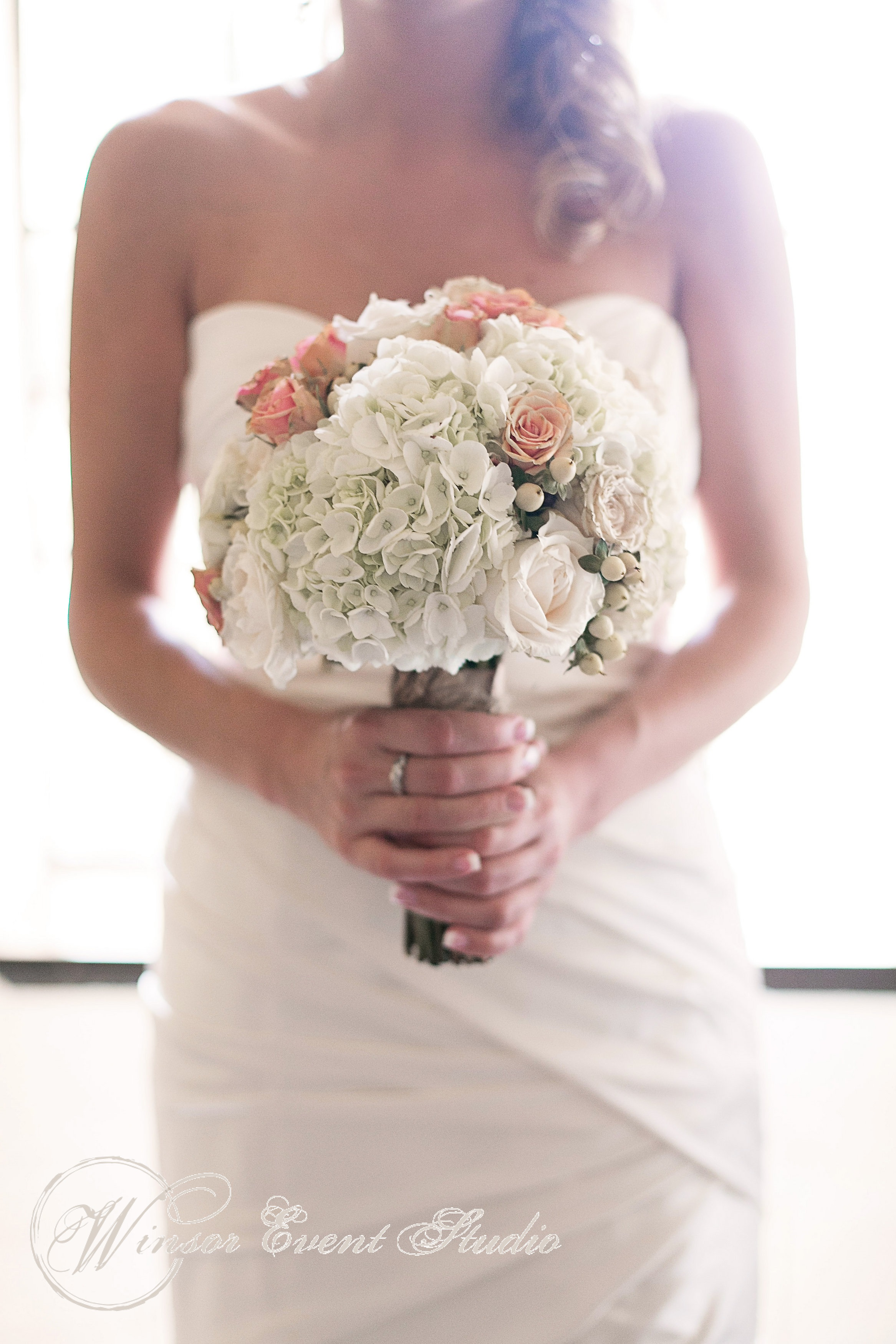 The bride carried a creamy bouquet of hydrangea, roses, and hypericum berries, dotted with nude pink roses
