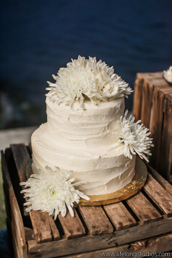 The simple wedding cake was adorned with crysanthemums and perched atop wood crates