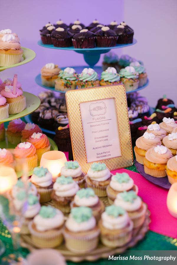Assorted cupcakes displayed in the dessert room were paired with champagne glasses of milk
