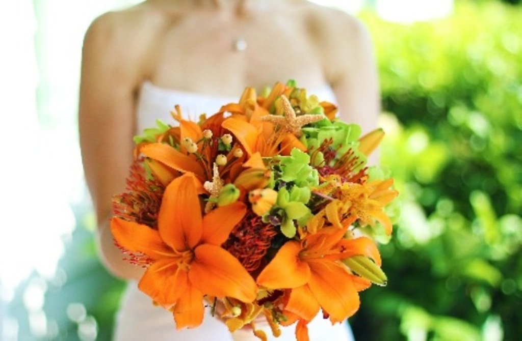 The bridal bouquet included lilies, protea, orchids, hypericum berries, and starfish