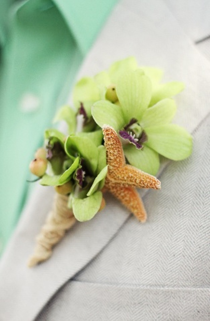 The groom's orchid boutonniere was wrapped with raffia and accented with a mini starfish