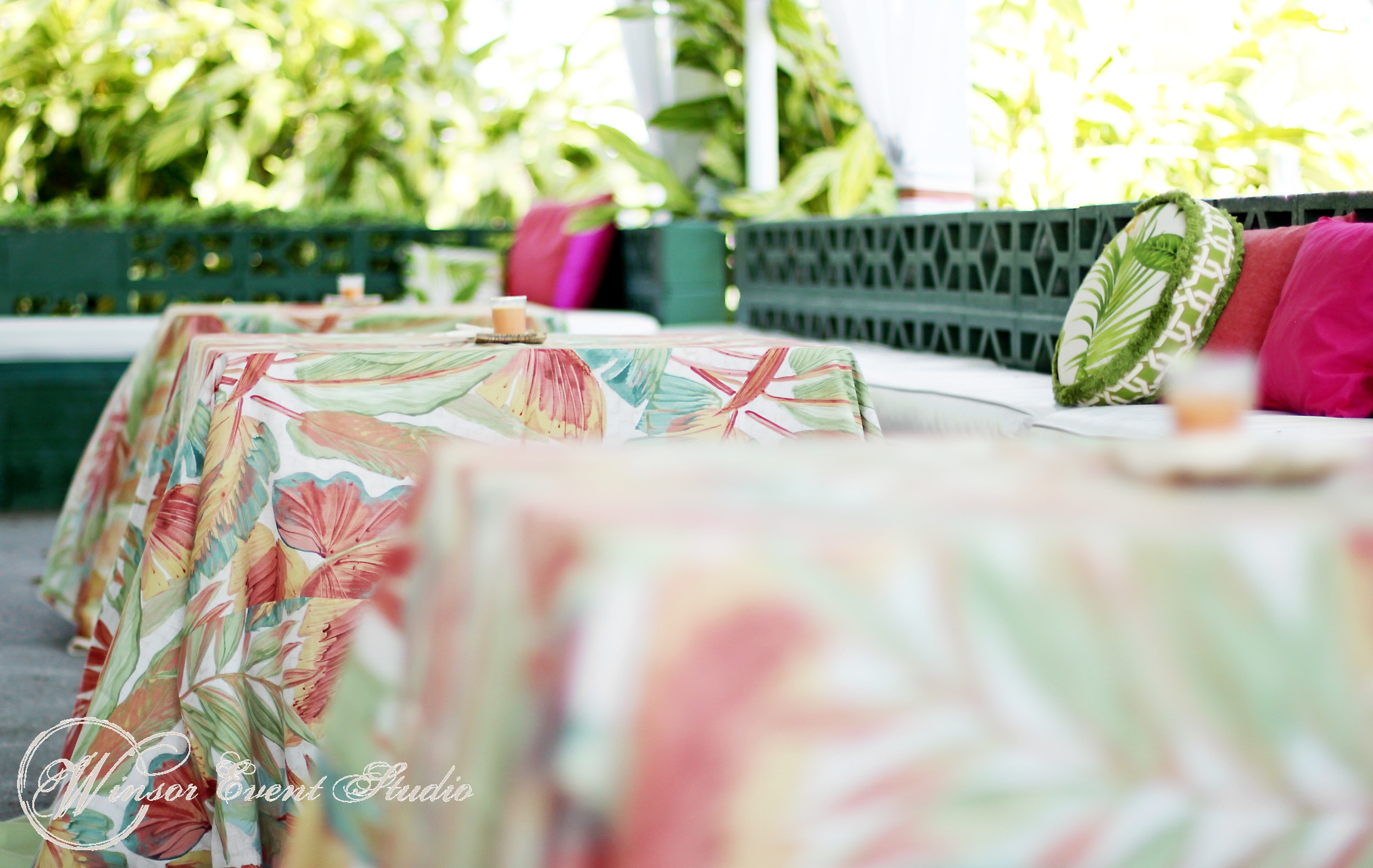 Cocktail tables were dressed in bright linens with a tropical motif, and the benches lined with colorful pillows