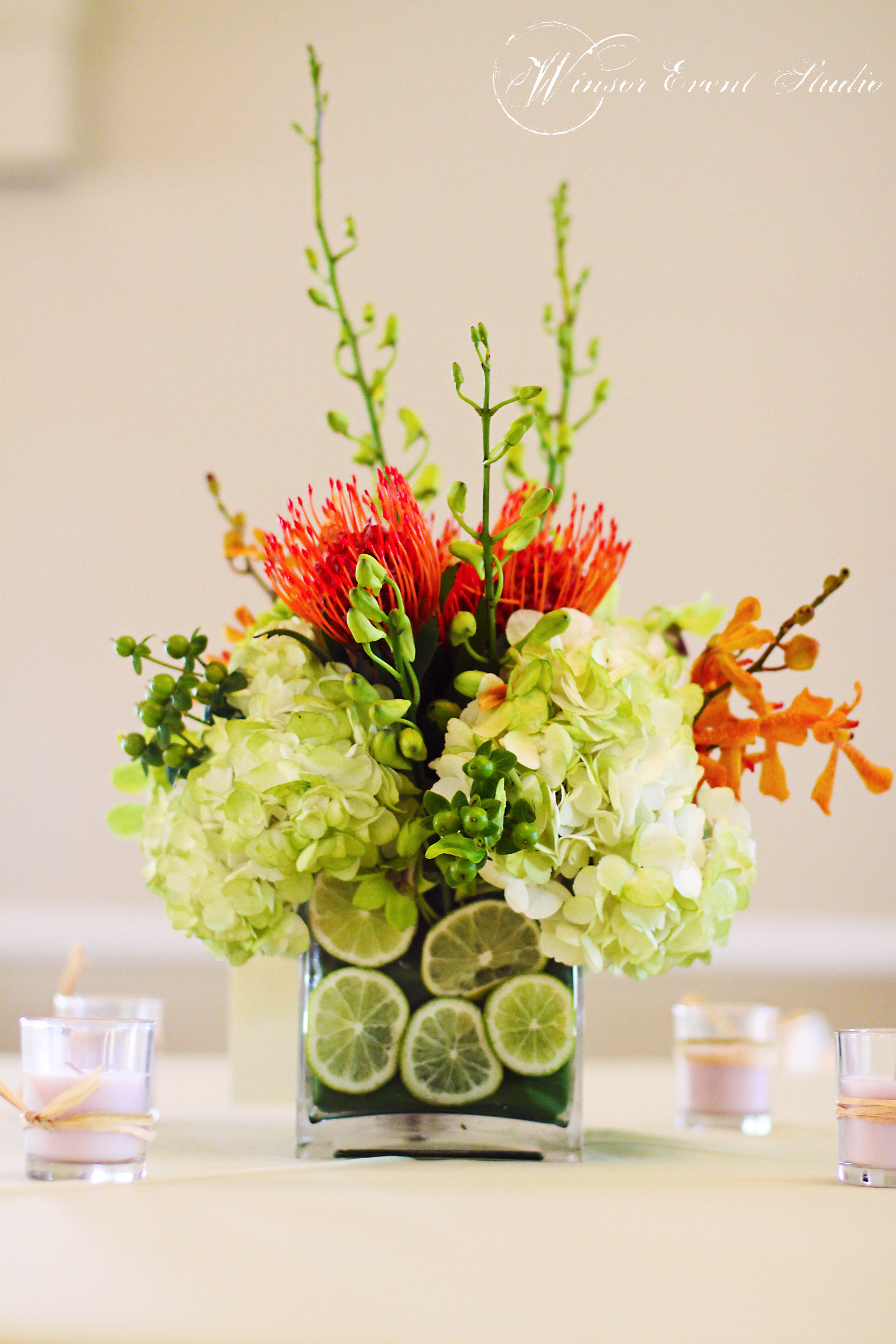 Centerpieces of hydrangea, protea, and orchids were displayed in vases filled with cut limes