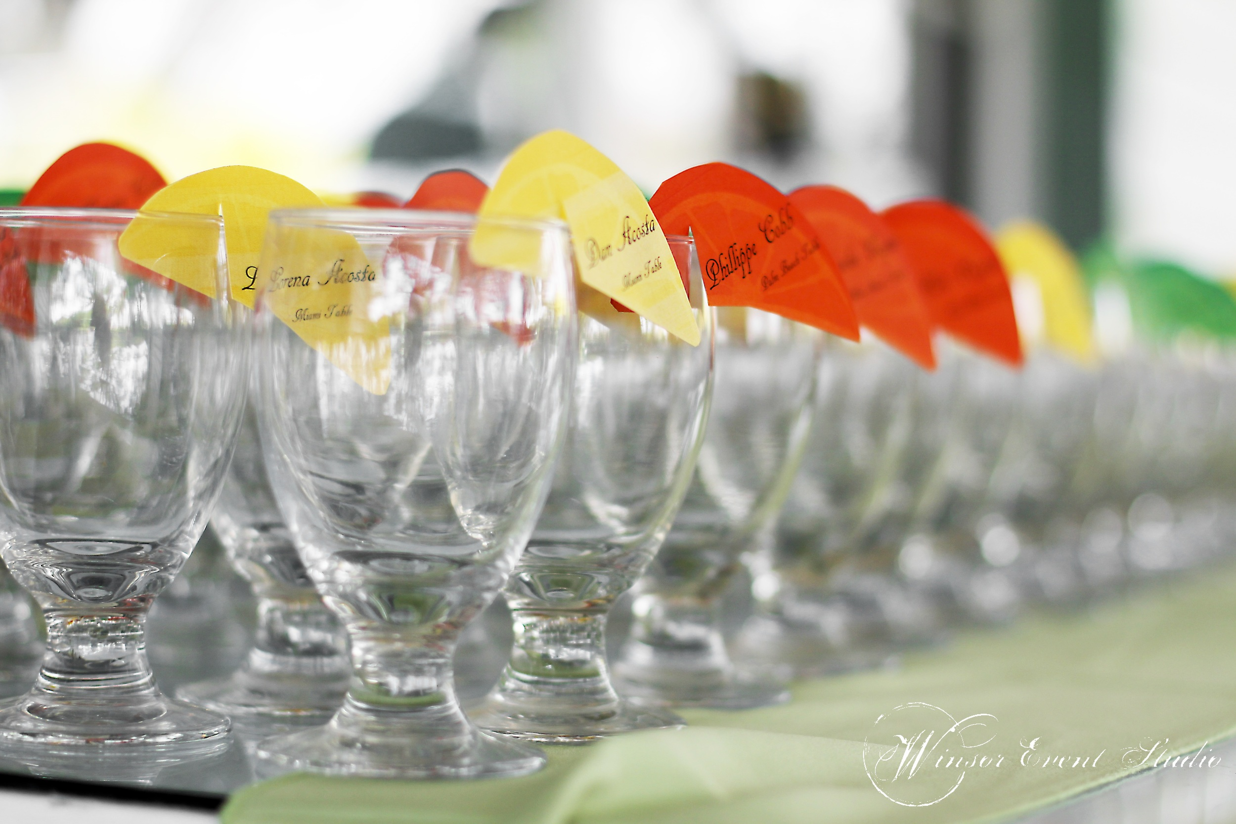 Citrus wedge escort cards perched atop rows of glasses were perfect for sipping tea during cocktail hour