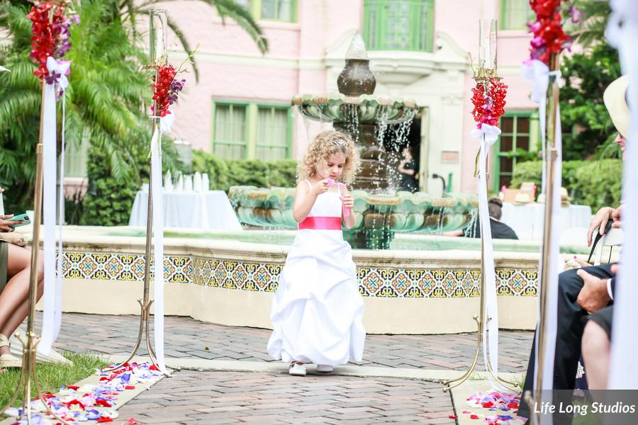 The aisle was lined with tall brass candlesticks tied with colorful orchids and flowing ribbons