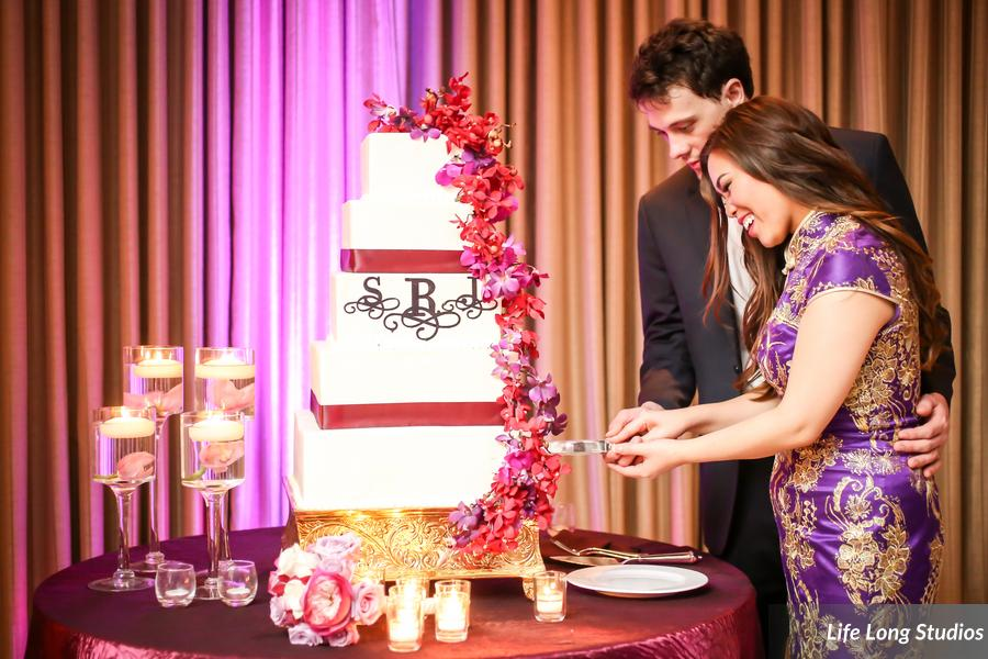 The bride changed into a Chinese silk gown before cutting into her 5 tier monogram and orchid studded cake