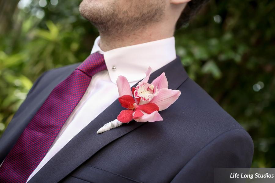 The groom sported a boutonniere pairing a pink cymbidium orchid with a red makara orchid