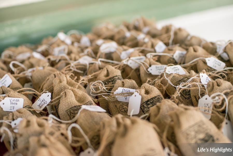 Stamped burlap sacks filled with chocolate covered espresso beans served as escort cards