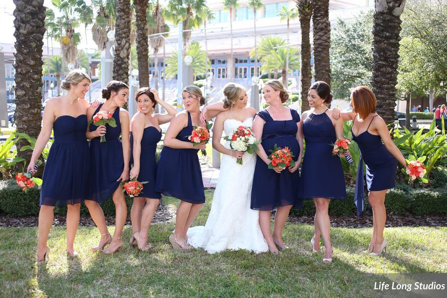 Bridesmaids wore mismatched navy dresses and carried coral bouquets