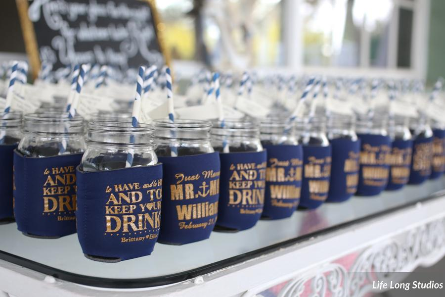 Mason jars with flagged straws tucked into koozies served as both favors and escort cards