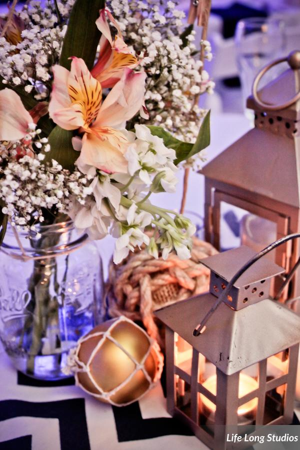 Gold lanterns, rope ball table numbers, and mason jars, were set atop navy chevron runners