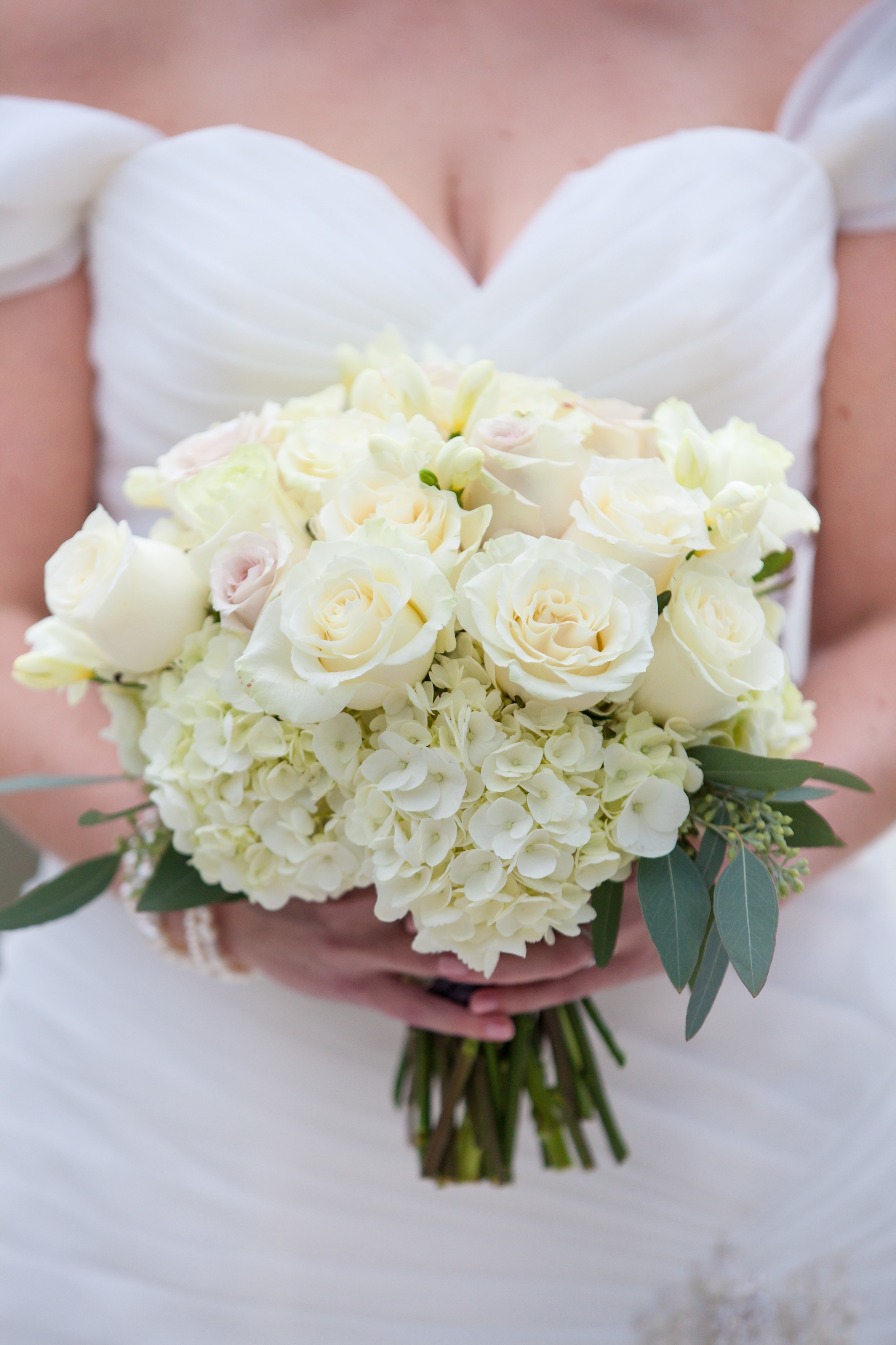 The bride's all white bouquet consisted of hydrangea and roses accented with seeded eucalyptus