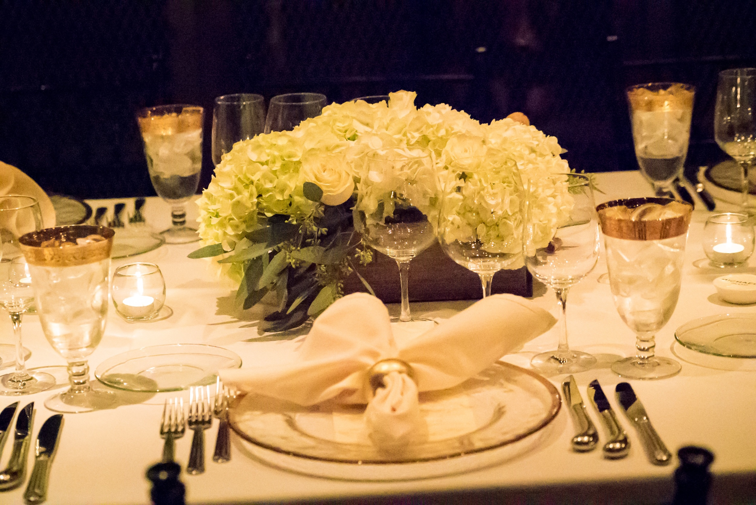 Place settings features gold-rimmed chargers and goblets, with hedge box centerpieces filled with natural flora