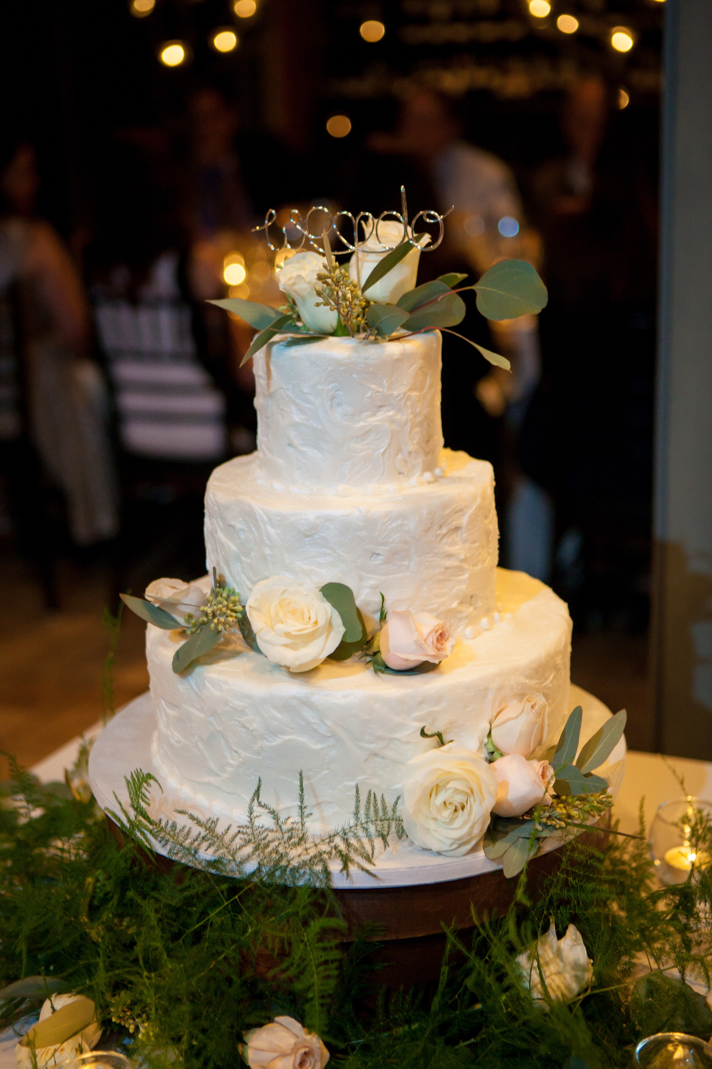 The wedding cake's textured buttercream icing was accented with fresh flowers and a wire topper