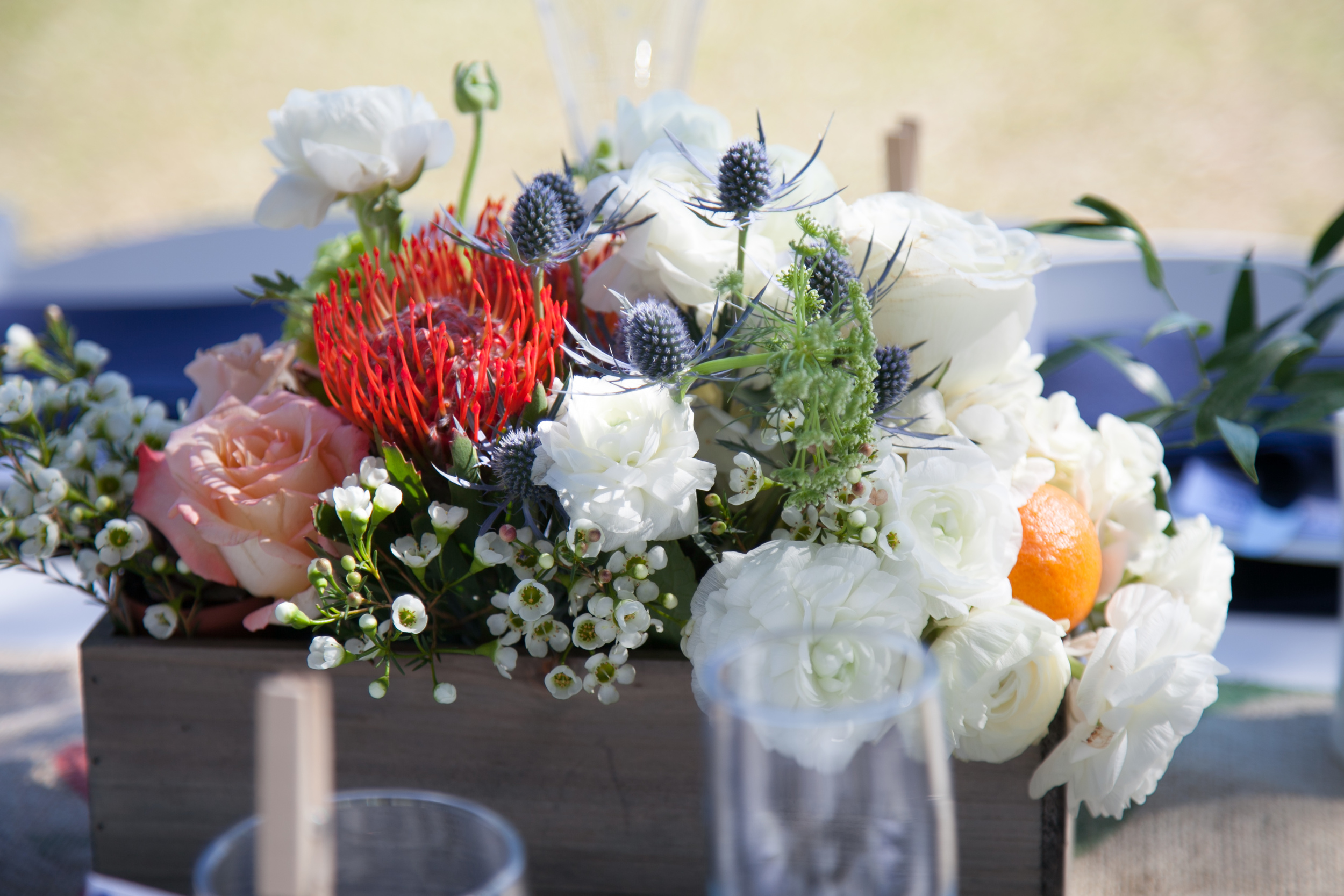 Hedgeboxes filled with assorted flowers like renunculus, blue thistle, and waxflower were accented with citrus