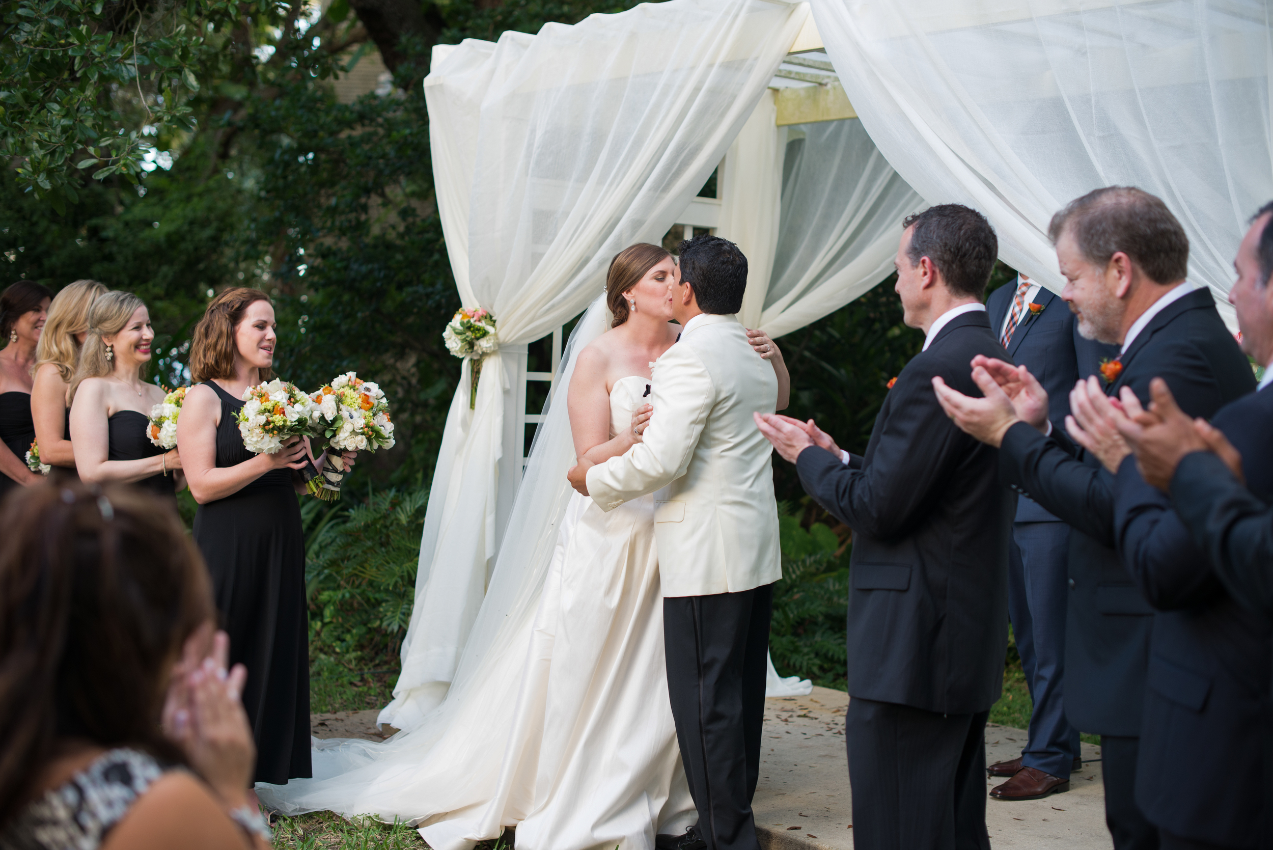 The bride's brother officiated the ceremony in front of a sheer draped arbor and their closest friends and family
